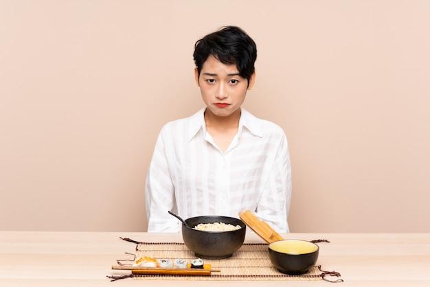 Jovem menina asiática em uma mesa com tigela de macarrão e sushi triste