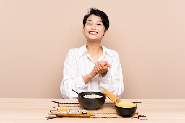 Jovem menina asiática em uma mesa com uma tigela de macarrão e sushi aplaudindo