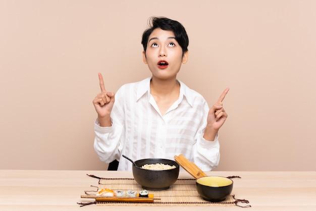 Jovem menina asiática em uma mesa com uma tigela de macarrão e sushi apontando com o dedo indicador uma ótima idéia
