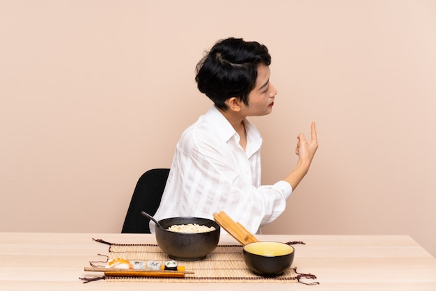 Jovem menina asiática em uma mesa com uma tigela de macarrão e sushi, apontando para trás com o dedo indicador