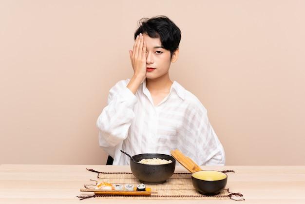 Jovem menina asiática em uma mesa com uma tigela de macarrão e sushi cobrindo um olho à mão