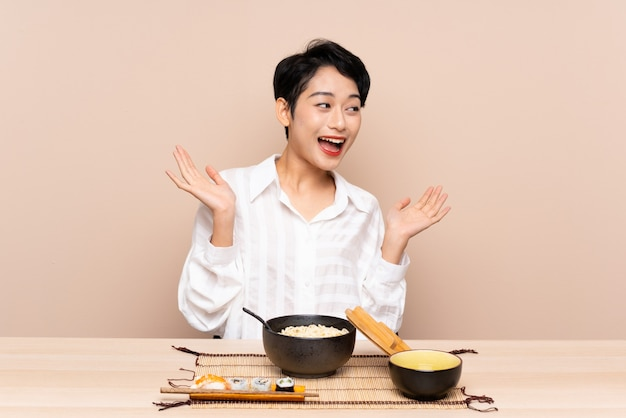 Jovem menina asiática em uma mesa com uma tigela de macarrão e sushi com expressão facial de surpresa