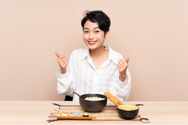 Jovem menina asiática em uma mesa com uma tigela de macarrão e sushi dando um polegar para cima gesto