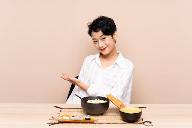 Jovem menina asiática em uma mesa com uma tigela de macarrão e sushi, estendendo as mãos para o lado para convidar para vir