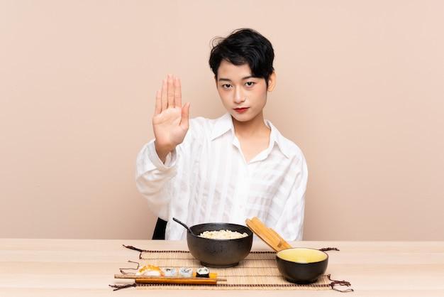 Jovem menina asiática em uma mesa com uma tigela de macarrão e sushi, fazendo o gesto de parada com a mão