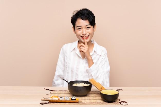 Jovem menina asiática em uma mesa com uma tigela de macarrão e sushi, fazendo o gesto de silêncio