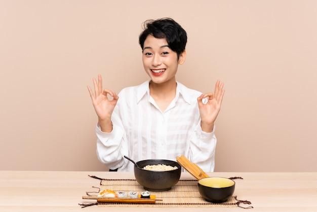 Jovem menina asiática em uma mesa com uma tigela de macarrão e sushi mostrando um sinal de ok com os dedos