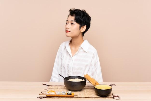 Jovem menina asiática em uma mesa com uma tigela de macarrão e sushi, olhando para o lado