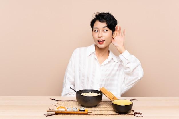 Jovem menina asiática em uma mesa com uma tigela de macarrão e sushi ouvindo algo