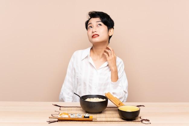 Jovem menina asiática em uma mesa com uma tigela de macarrão e sushi, pensando uma idéia