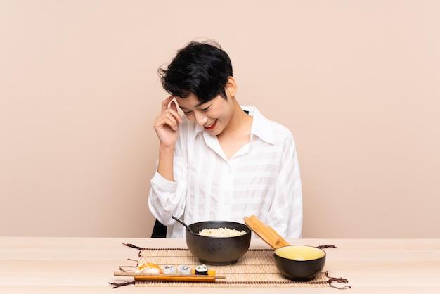 Jovem menina asiática em uma mesa com uma tigela de macarrão e sushi rindo