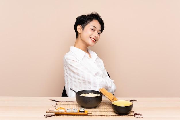 Jovem menina asiática em uma mesa com uma tigela de macarrão e sushi