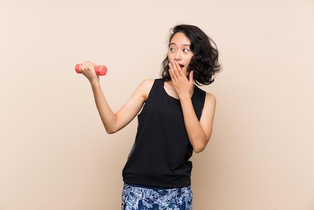 Jovem menina asiática fazendo levantamento de peso com surpresa e expressão facial chocada