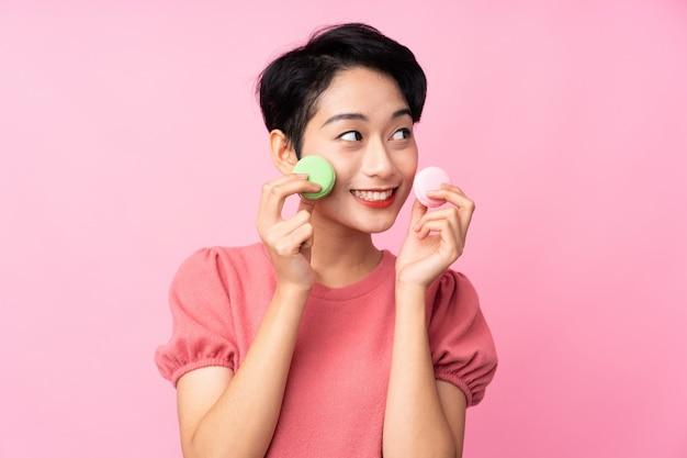 Jovem menina asiática isolado parede rosa segurando macarons franceses coloridos e olhando para cima