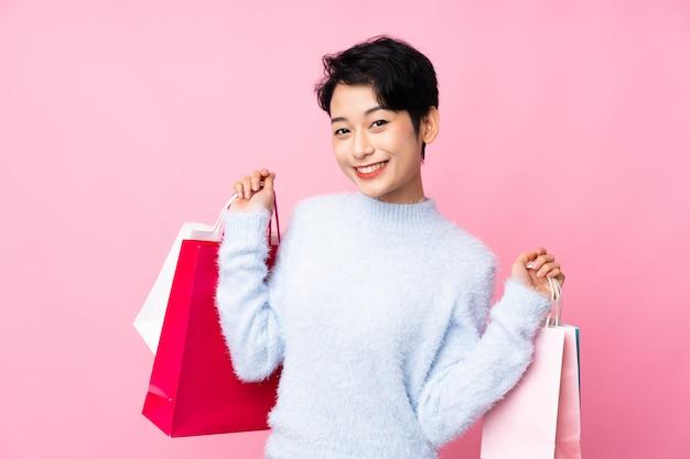 Jovem menina asiática isolado parede rosa segurando sacolas de compras e sorrindo