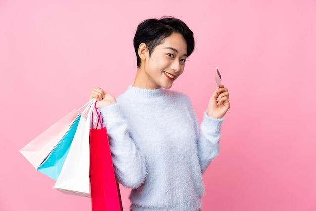 Jovem menina asiática isolado parede rosa segurando sacolas de compras e um cartão de crédito