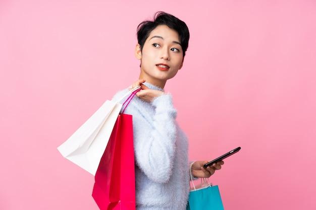 Jovem menina asiática isolado parede rosa segurando sacolas de compras e um telefone móvel