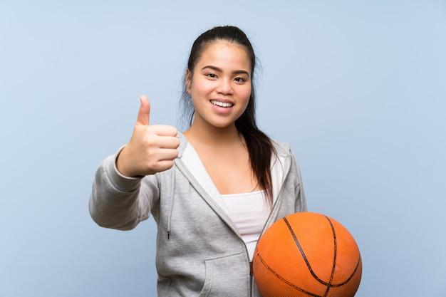 Jovem menina asiática jogando basquete na parede isolada com polegares para cima porque algo bom aconteceu