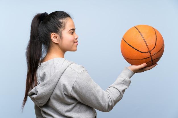 Jovem menina asiática jogando basquete na parede isolada