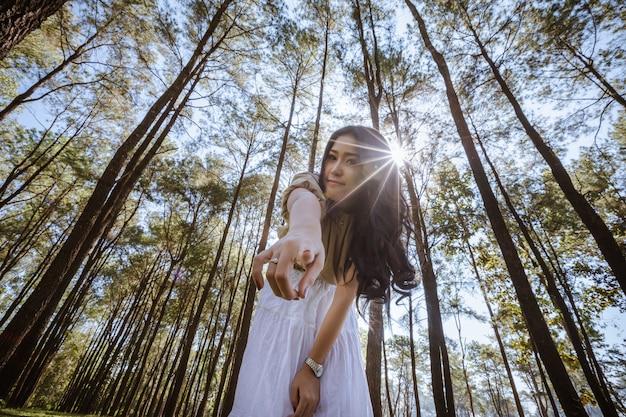 Jovem menina asiática muito feliz e sorridente no jardim e de mãos dadas