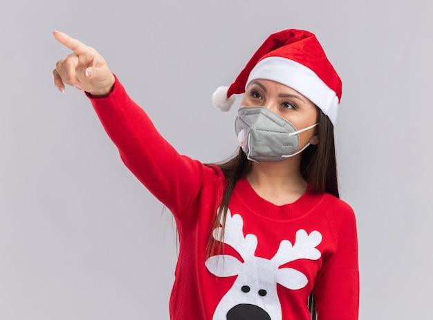 Jovem menina asiática olhando satisfeita com um chapéu de natal com suéter e máscara médica apontando para o lado isolado no fundo branco
