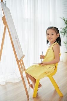 Jovem menina asiática posando em casa na frente do cavalete, com pincel e aquarelas
