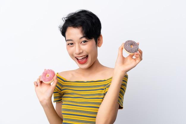 Jovem menina asiática segurando donuts com expressão feliz