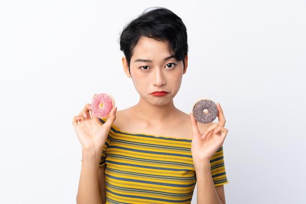 Jovem menina asiática segurando donuts com expressão triste