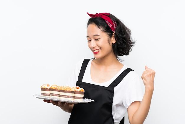 Jovem menina asiática segurando lotes de bolo de muffin sobre parede branca comemorando uma vitória