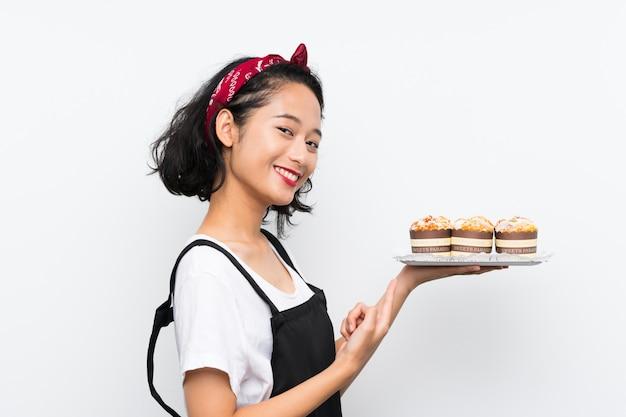 Jovem menina asiática segurando lotes de bolo de muffin sobre parede branca e apontando-o