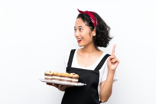 Jovem menina asiática segurando lotes de bolo de muffin sobre parede branca isolada, com a intenção de realizar a solução enquanto levanta um dedo