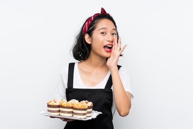 Jovem menina asiática segurando lotes de bolo muffin sobre parede branca, gritando com a boca aberta