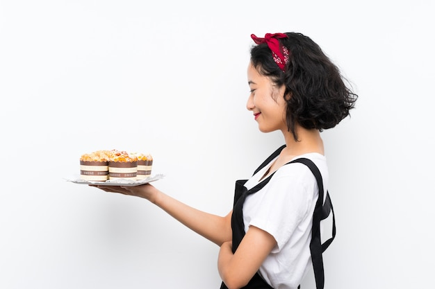 Jovem menina asiática segurando lotes de bolo muffin sobre parede branca isolada com expressão feliz