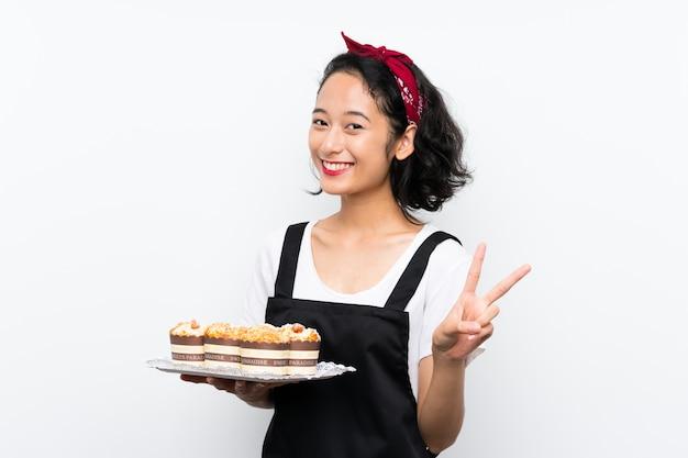 Jovem menina asiática segurando lotes de bolo muffin sobre parede branca, sorrindo e mostrando sinal de vitória
