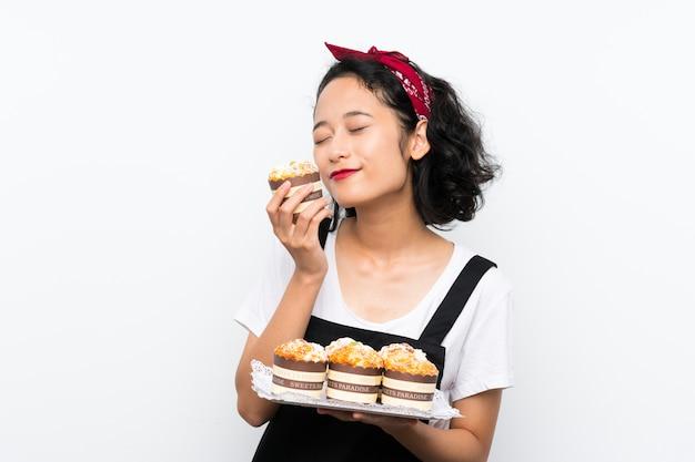 Jovem menina asiática segurando lotes de bolo muffin sobre parede branca