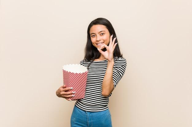 Jovem menina asiática segurando um balde de pipoca alegre e confiante mostrando um gesto de ok.