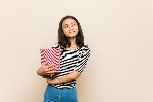 Jovem menina asiática segurando um balde de pipoca, sorrindo confiante com os braços cruzados.