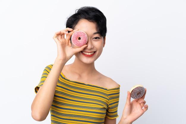 Jovem menina asiática segurando um donut e feliz