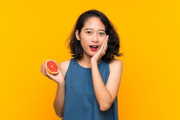 Jovem menina asiática segurando uma toranja com surpresa e expressão facial chocada