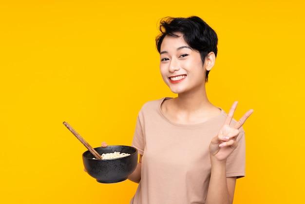 Jovem menina asiática sobre parede amarela isolada, sorrindo e mostrando sinal de vitória, mantendo uma tigela de macarrão com pauzinhos