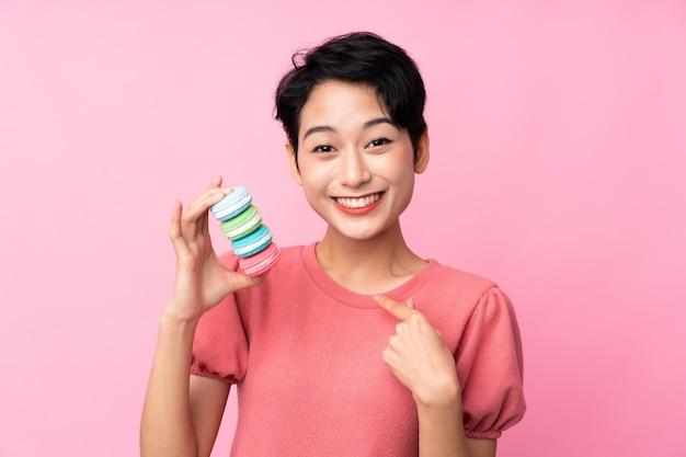 Jovem menina asiática sobre parede rosa isolada segurando macarons franceses coloridos com expressão de surpresa