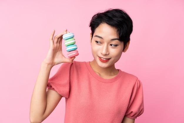 Jovem menina asiática sobre parede rosa isolada segurando macarons franceses coloridos e com expressão feliz