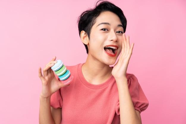 Jovem menina asiática sobre parede rosa isolada segurando macarons franceses coloridos e gritando