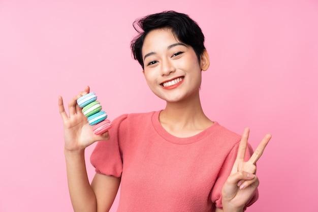 Jovem menina asiática sobre parede rosa isolada segurando macarons franceses coloridos e mostrando sinal de vitória