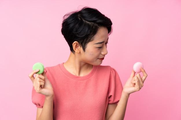 Jovem menina asiática sobre parede rosa isolada segurando macarons franceses coloridos e olhando