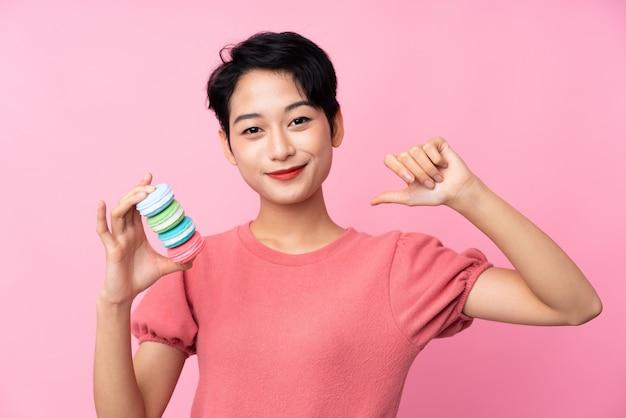 Jovem menina asiática sobre parede rosa isolada segurando macarons franceses coloridos e orgulhoso