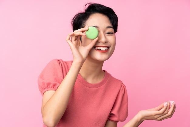 Jovem menina asiática sobre parede rosa isolada segurando macarons franceses coloridos