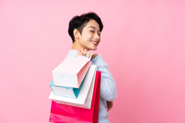 Jovem menina asiática sobre parede rosa isolada segurando sacolas de compras e sorrindo