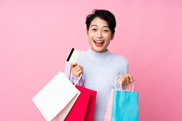 Jovem menina asiática sobre parede rosa isolada segurando sacolas de compras e surpreso