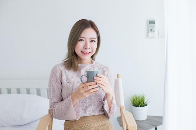 Jovem menina asiática tomando café no quarto